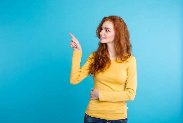 Close-up portret jonge mooie aantrekkelijke roodharige meisje blij met iets en wijst vinger. blauwe pastelachtergrond. kopieer de ruimte. Gratis Foto