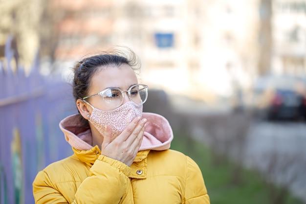 Close-up portret jonge vrouw in een masker tijdens het pandemische coronavirus. Gratis Foto