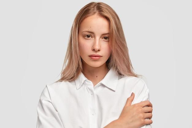 Close-up portret van aantrekkelijk europees vrouwelijk model houdt de handen gekruist en kijkt met zekere uitdrukking rechtstreeks in de camera Gratis Foto