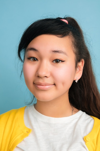 Close-up portret van aziatische tiener geïsoleerd op blauwe studio Gratis Foto
