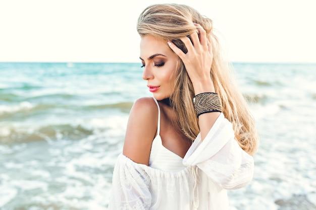 Close-up portret van blond meisje met lang haar dromen op zee achtergrond. ze draagt witte kleren en versieringen bij de hand. ze kijkt naar beneden. Gratis Foto