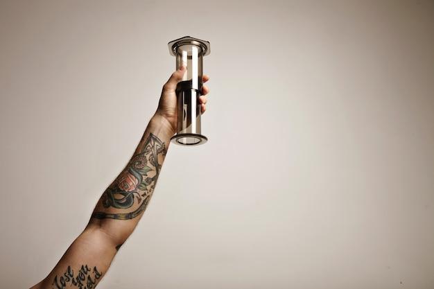 Close-up portret van de hand van een getatoeëerde man met heldere lichtgrijze aeropress niet-traditionele koffiezetapparatuur hoog in de lucht geïsoleerd op wit Gratis Foto