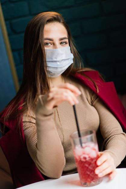 Close-up portret van een blanke vrouw die een medisch masker draagt en in de straat staat tegen de achtergrond van een café Premium Foto