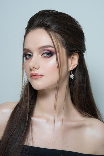 Close-up portret van een jonge mooie vrouw. close-up portret van een mooie jonge brunette vrouw met lang haar en avond make-up Premium Foto