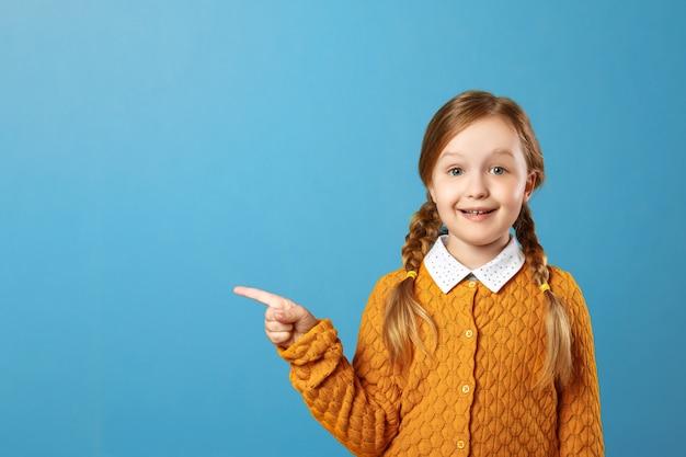 Close-up portret van een klein meisje schoolmeisje op een blauwe achtergrond Premium Foto