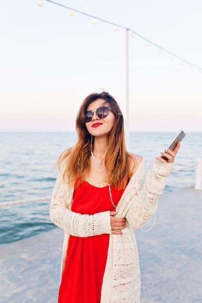 Close-up portret van een mooi meisje in een rode jurk en witte jas op een pier, glimlachend en luisteren naar muziek op oortelefoons op een smartphon Gratis Foto