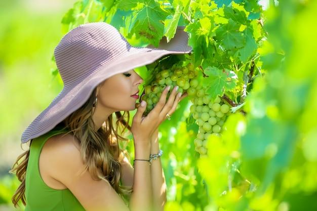 Close-up portret van een mooie jonge vrouw die een tros druiven in haar handen houdt Premium Foto
