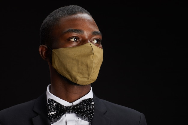 Close-up portret van elegante afro-amerikaanse man met gezichtsmasker terwijl poseren tegen zwarte achtergrond op feestje, kopieer ruimte Premium Foto