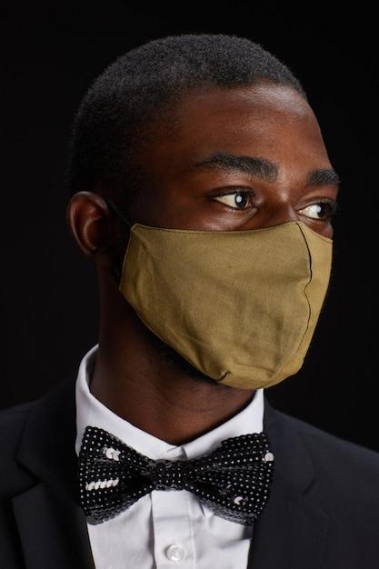 Close-up portret van elegante afro-amerikaanse man met gezichtsmasker terwijl poseren tegen zwarte achtergrond op feestje Premium Foto