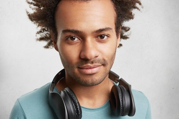 Close-up portret van gemengd ras donkere man met haren en donkere ogen, heeft koptelefoon Gratis Foto