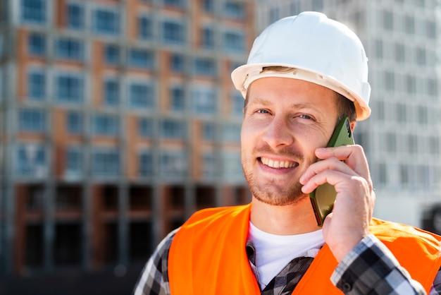 Close-up portret van ingenieur praten aan de telefoon Gratis Foto