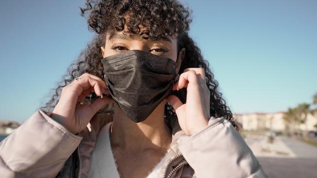 Close-up portret van jonge afro-amerikaanse vrouw terwijl het dragen van een zwart masker om coronavirus-infectie te voorkomen. Premium Foto