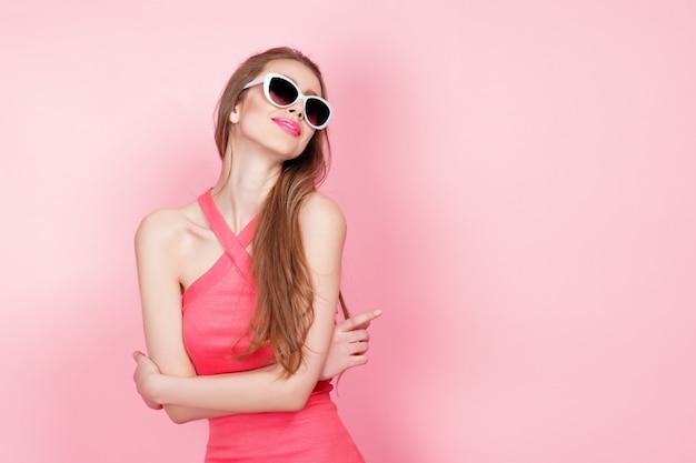 Close-up portret van jonge mooie slanke sexy jonge vrouw in sexy jurk met rode sensuele lippen op roze draagt een zonnebril. glimlachend en poseren Premium Foto