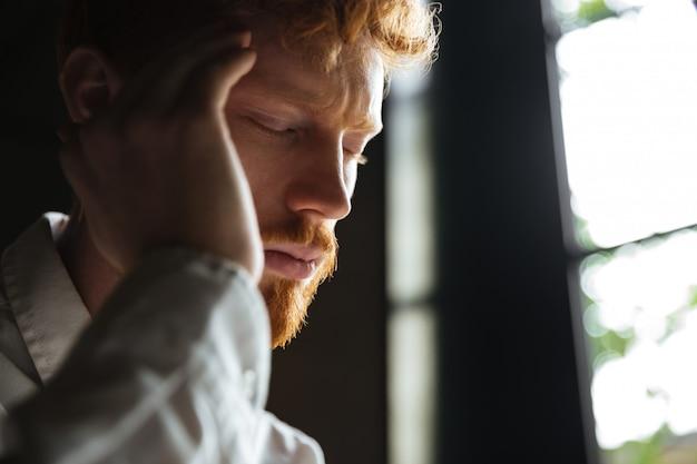 Close-up portret van jonge roodharige man met hoofdpijn, zijn hoofd aan te raken Gratis Foto