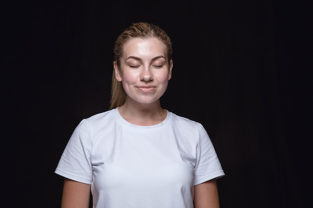 Close-up portret van jonge vrouw geïsoleerd. vrouwelijk model met gesloten ogen. denken en glimlachen. gelaatsuitdrukking, concept van menselijke emoties. Gratis Foto