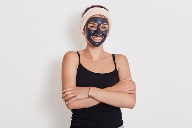 Close-up portret van jonge vrouw past zelfgemaakte gezichts klei masker toe, heeft witte haarband om het hoofd, lacht vrolijk, houdt handen gevouwen tegen witte muur Gratis Foto