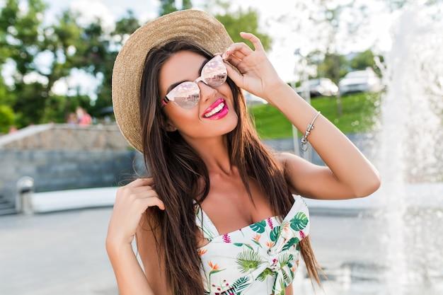 Close-up portret van mooie brunette meisje met lang haar poseren voor de camera in park in de buurt van fonteinen. ze raakt haar zonnebril aan en lacht. Gratis Foto