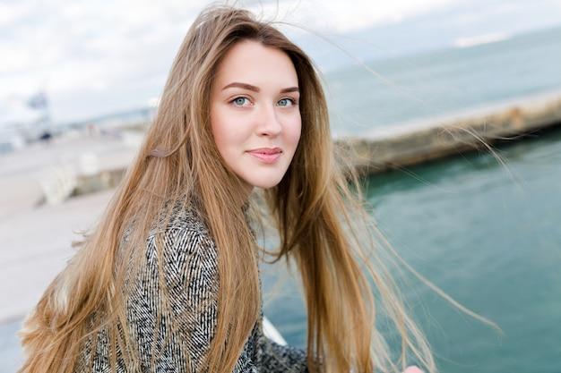 Close-up portret van mooie charmante vrouw met een gelukkige glimlach loopt in de buurt van de zee Gratis Foto
