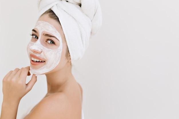 Close-up portret van mooie jonge vrouw met handdoeken na bad nemen cosmetische masker op haar gezicht. Gratis Foto