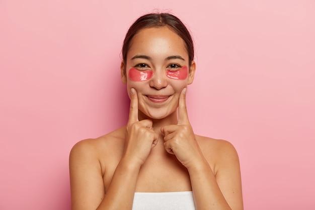 Close-up portret van mooie koreaanse vrouw draagt cosmetische plekken onder de ogen voor wallen, houdt de wijsvingers op de wangen, lacht zachtjes, poseert shirtless, vermijdt donkere kringen en rimpels op het gezicht Gratis Foto