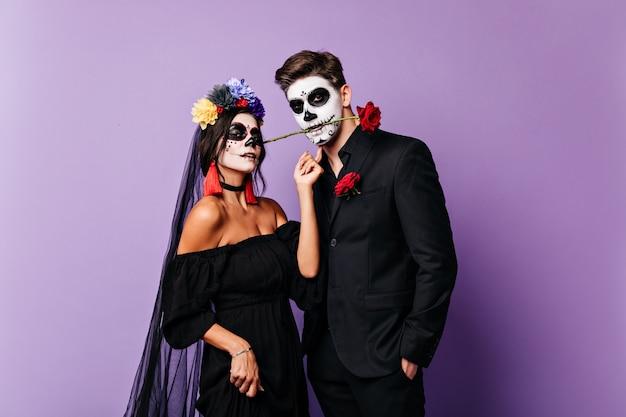 Close-up portret van paar liefhebbers in feestelijke carnaval kostuums poseren op paarse achtergrond. gepassioneerde mexicaanse man houdt roos tussen zijn tanden terwijl zijn bruid in de camera kijkt. Gratis Foto
