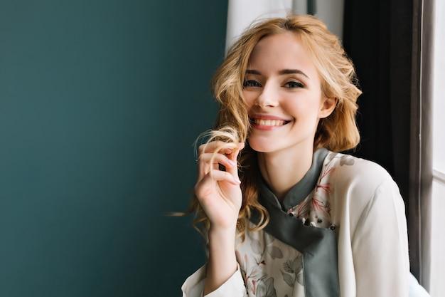 Close-up portret van prachtige blonde jonge vrouw, gekleed in turkooizen pyjama's, zittend naast het raam. ze is blij, lacht en raakt haar golvende haar aan. Gratis Foto