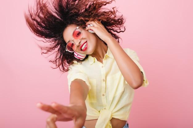 Close-up portret van schattig krullend meisje gelukkig lachend. prachtige afrikaanse vrouw met lichtbruine huid ontspannen in hoofdtelefoons en grappig dansen. Gratis Foto