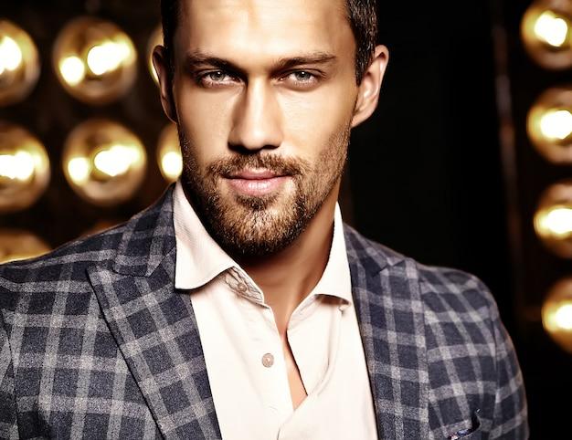 Close-up portret van sexy knappe mode mannelijk model man gekleed in elegant pak op zwarte studio lichten achtergrond Gratis Foto
