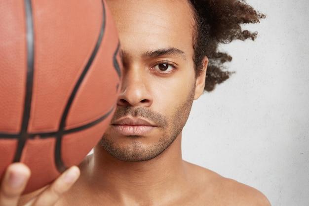 Close-up portret van succesvolle basketbalspeler houdt bal op voorgrond Gratis Foto