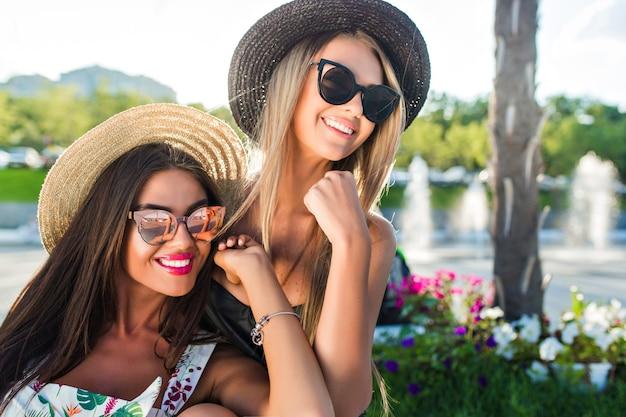 Close-up portret van twee aantrekkelijke blonde en brunette meisjes met lang haar poseren voor de camera in park. ze glimlachen opzij. Gratis Foto