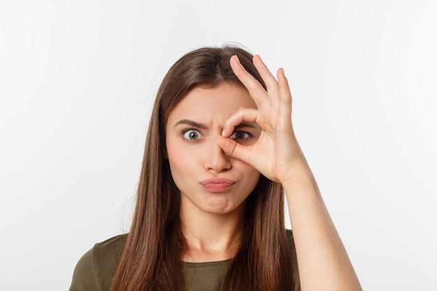 Close-up portret van vrolijke, leuke, stijlvolle, aantrekkelijke, trendy meisje verrekijker met vingers maken, geïsoleerd op grijze achtergrond, goed humeur Premium Foto