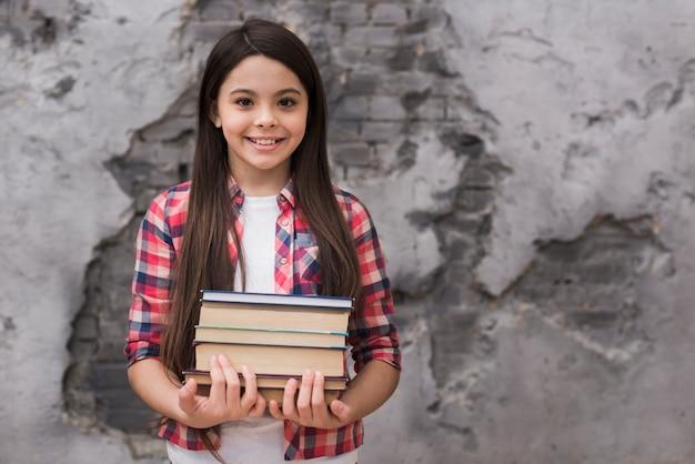 Close-up positief jong meisje dat een stapel boeken houdt Gratis Foto