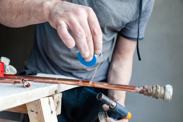 Close-up professionele hoofdloodgieter met fluxpasta voor solderen en solderen van naden van koperen pijpgasbrander. Premium Foto