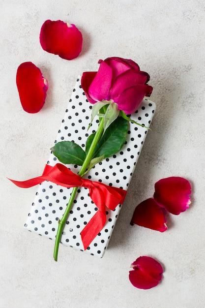 Close-up rode roos bovenop cadeau Gratis Foto