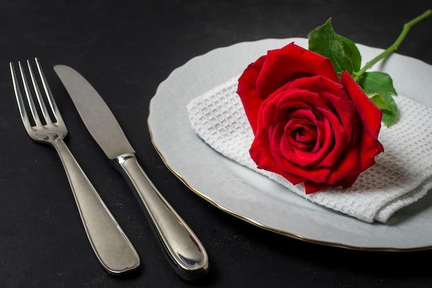 Close-up rode roos op een bord met bestek Gratis Foto