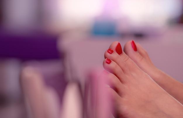 Close-up rode teennagels van vrouw in nagelsalon. rode gel kleur teennagel pedicure op nagel en spa salon. voetverzorging en teennagelbehandeling bij nagelsalon. feministische zaken. schoonheid en mode concept. Premium Foto