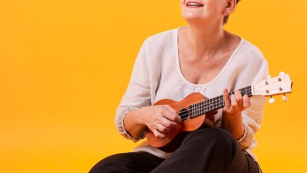 Close-up senior vrouw gitaar spelen Gratis Foto