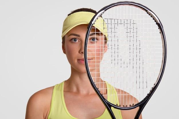 Close-up shot van aangenaam ogende gezonde vrouw houdt tennisracket, wordt runner up, kijkt door net, draagt court cap Gratis Foto