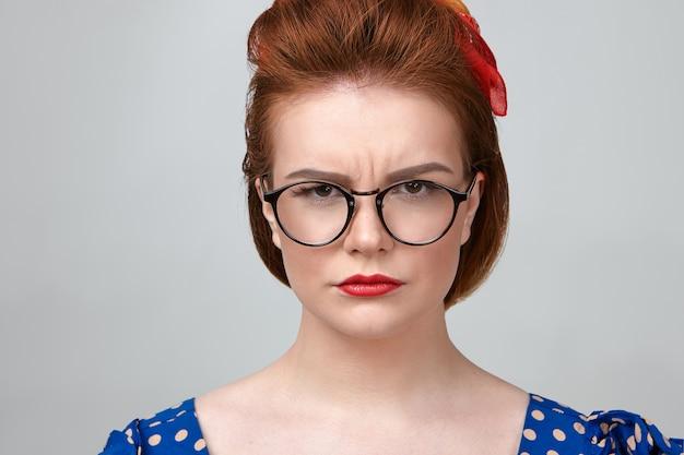 Close-up shot van aantrekkelijke jonge blanke vrouwelijke leraar dragen gestippelde jurk, rode lippenstift en stijlvolle bril fronsen, camera kijken met strikte uitdrukking, geïrriteerd met luidruchtige leerlingen Gratis Foto