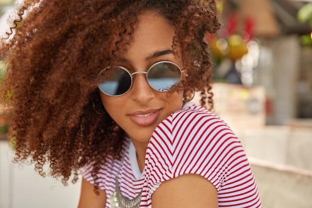 Close-up shot van aantrekkelijke vrouw met krullend haar, draagt ronde trendy tinten, casual t-shirt, geniet van de zomertijd, heeft een eigen stijl, houdt van modieuze kleding Gratis Foto
