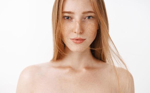 Close-up shot van aantrekkelijke vrouwelijke naakte roodharige vrouw met sproeten sensueel poseren met sexy blik in de ogen permanent durven vertrouwen in eigen lichaam Gratis Foto