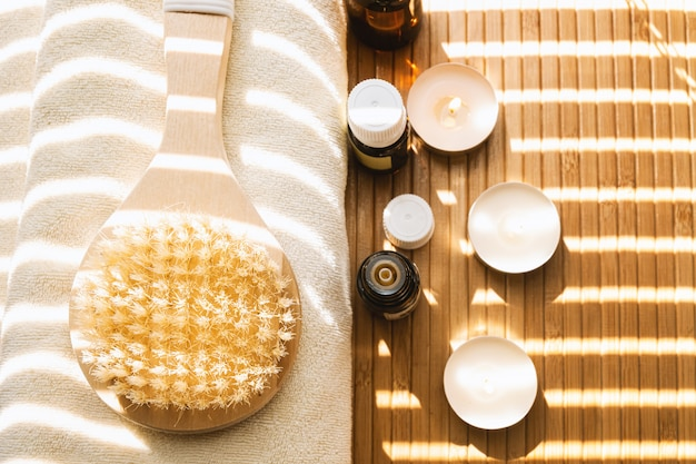 Close-up shot van badborstel met etherische oliën en kaarsen. spa concept. Gratis Foto