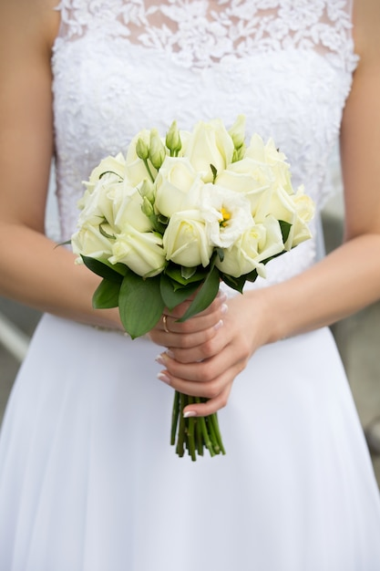 Close-up shot van bruid handen met mooie bruiloft boeket met groene rozen Premium Foto
