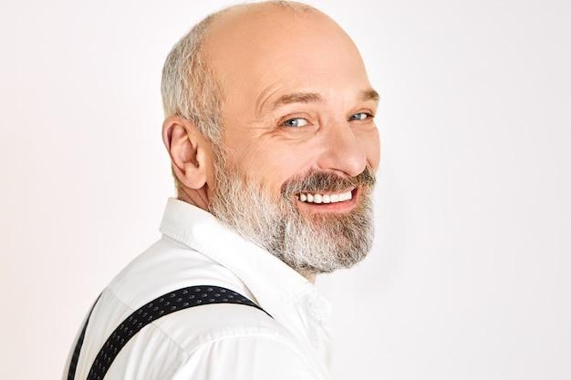 Close-up shot van charismatische vrolijke europese mannelijke gepensioneerde m / v met borstelige baard elegante stijlvolle kleding dragen bij speciale gelegenheid in goed humeur, camera kijken met brede stralende glimlach Gratis Foto