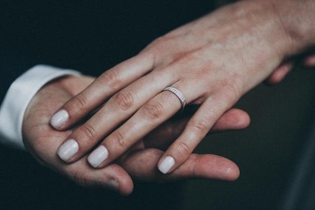 Close-up shot van de hand van een vrouw met zilveren ring aan de hand van een man met een onscherpe achtergrond Gratis Foto