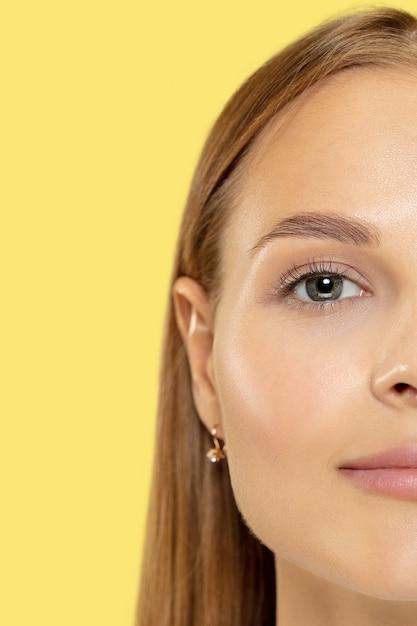Close-up shot van de kaukasische jonge vrouw op gele studio Gratis Foto