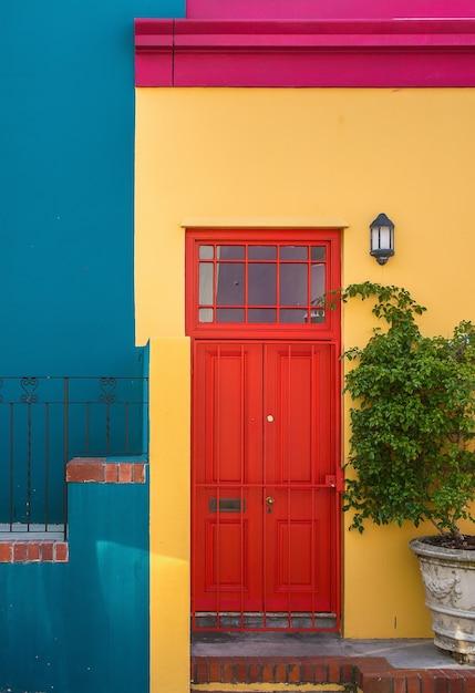 Close-up shot van de rode deur van een geel gebouw en een plant ernaast Gratis Foto