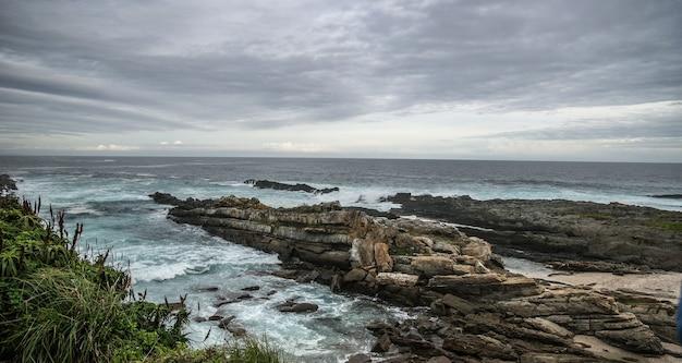 Close-up shot van de rotsen op een strand onder een hemel vol wolken Gratis Foto