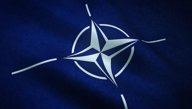 Close-up shot van de wapperende vlag van de noord-atlantische verdragsorganisatie met interessante texturen Gratis Foto