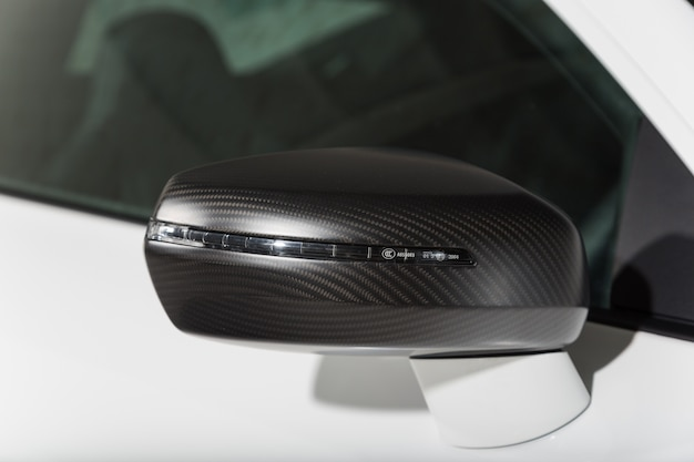 Close-up shot van de zwarte zijspiegel van een moderne witte auto Gratis Foto